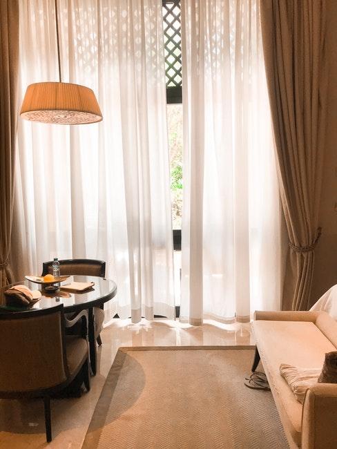 Salon avec méridienne couleur pêche, suspension crème, rideaux occultants et tapis taupe