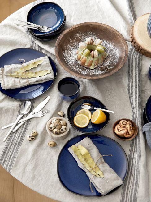 Table avec une nappe en lin et assiettes bleu foncé à forme inégale, à bord noir