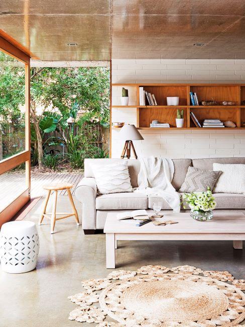 Salon-véranda, avec tabouret en métal blanc, canapé gris, table basse blanche et étagères murales en bois