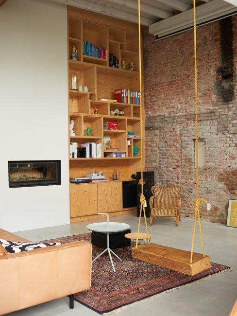 Salon avec balançoire en bois et mur de brique apparente brute