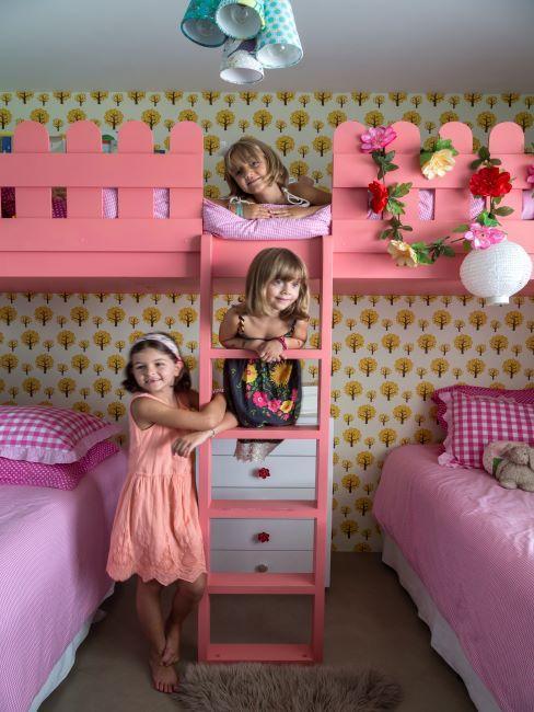 Trois petites filles dans leur chambre avec papier peint graphique et lit superposé rose