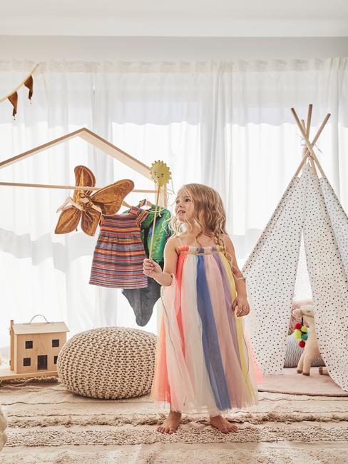 petite fille dans une salle de jeux air rêveuse et joue avec un papillon en ours