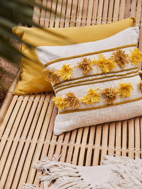 Coussins décoratifs jaunes sur transat en bois