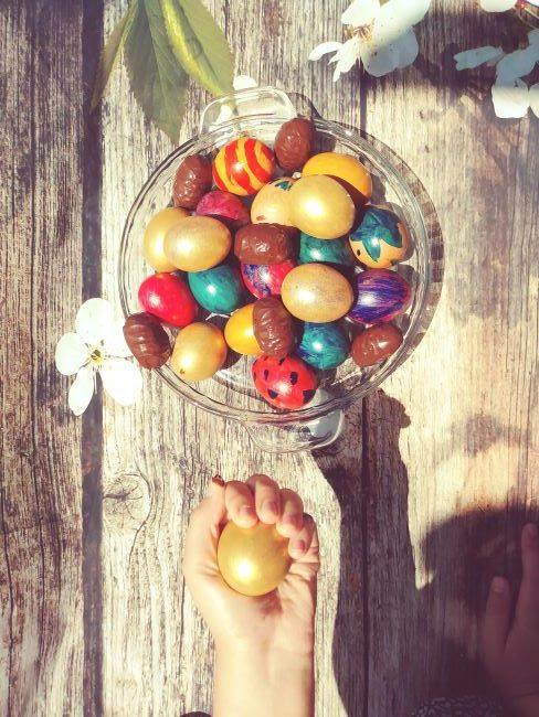 Bol avec œufs de Pâques en chocolat et main d'enfant tenant un œuf