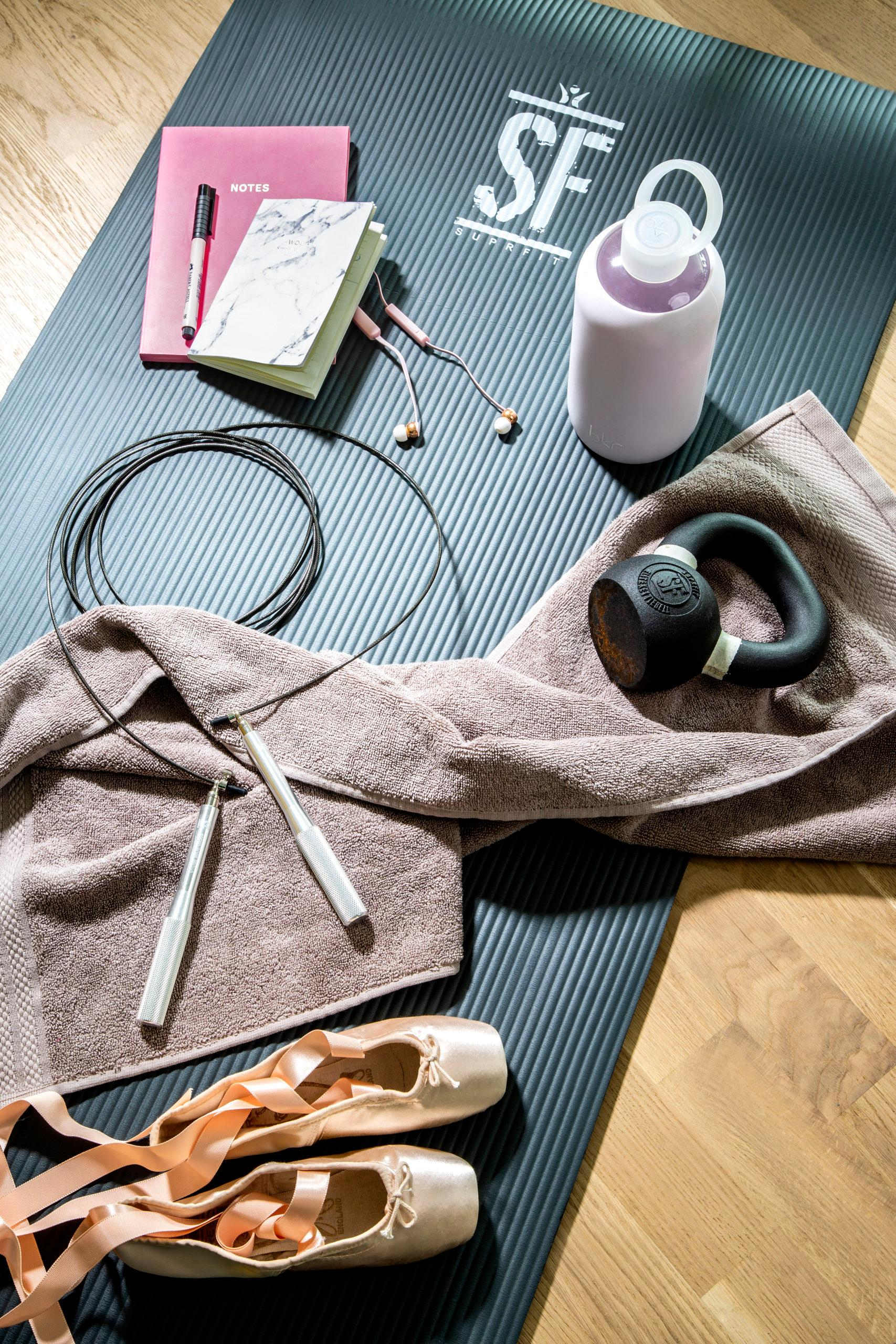 tapis d'exercices avec une corde a sauter, une paire de ballerines, un poids, des ecouteurs et une gourde