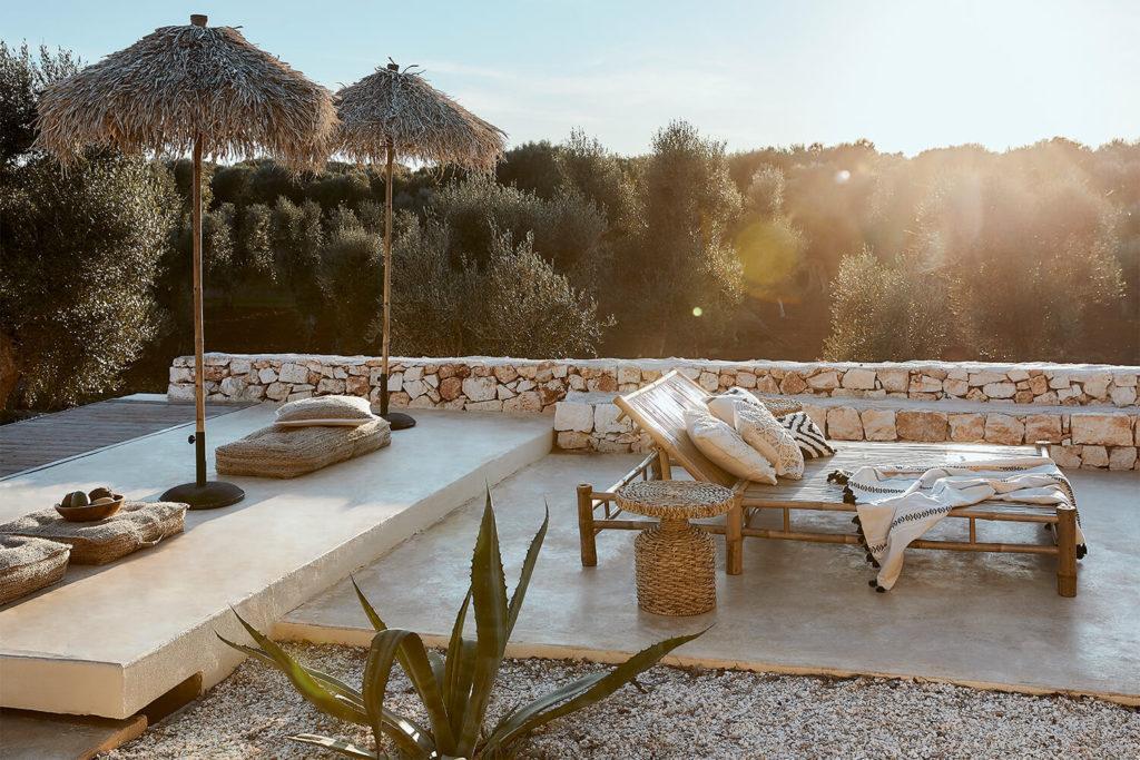 Terrasse ambiance majorque transat double en bois et parasols de paille