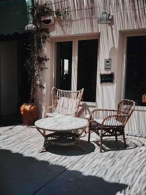 table basse ronde en bois avec deux chaises en rotin