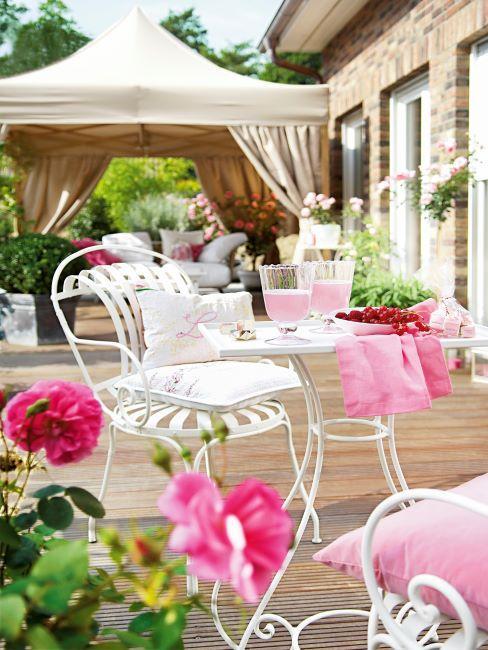 jolie petite table carree blanche en metal avec une chaise dans le meme style, decoree d'une nappe rose clair et coussins de la meme couleur, fleurs roses