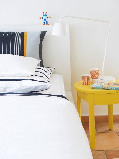 lit avec lange blanc et coussin decoratif raye et table de chevet jaune citron