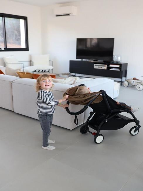 Petite fille avec une poussette avec vue sur le coin salon blanc