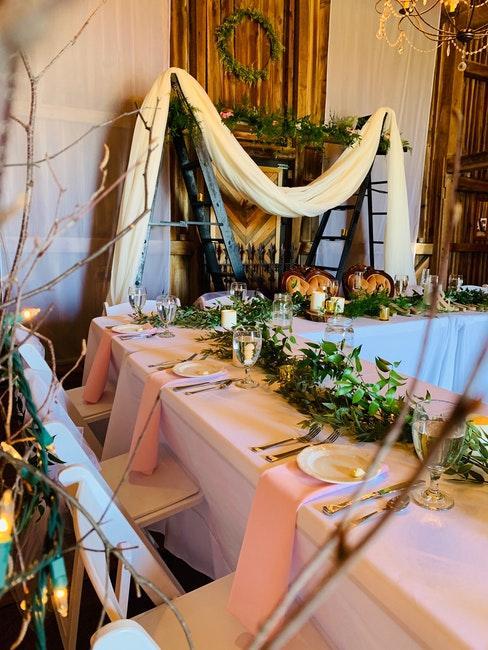 Table de mariage rectangulaire decoree de fleurs avec nappe et serviettes de table roses