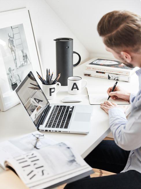 laptop, ordinateur pose sur un bureau, mug avec lettre A et pichet isotherme, un homme en train d ecrire avec un stylo