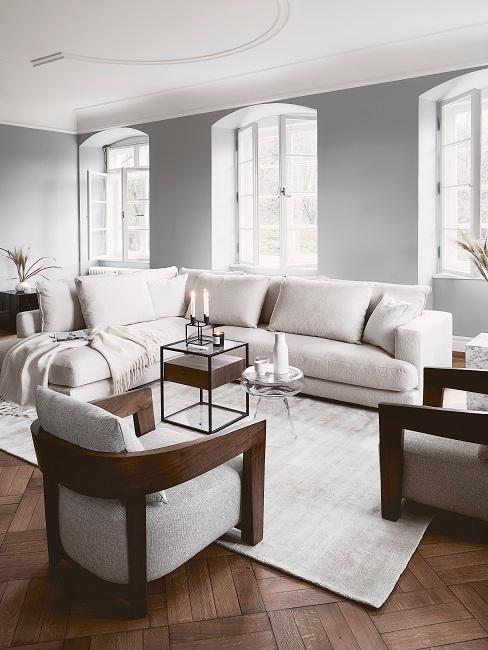 Soggiorno arredato in modo minimalista con divano ad angolo beige e due comode poltrone in tessuto e legno chiaro.