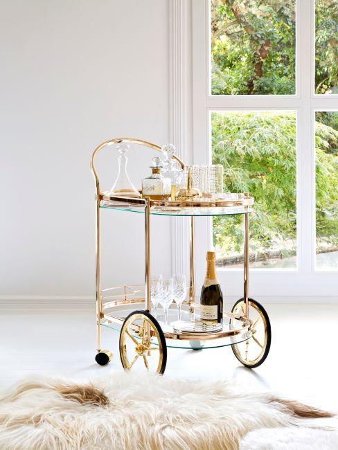 carrello bar dorato con bottiglia e bicchieri