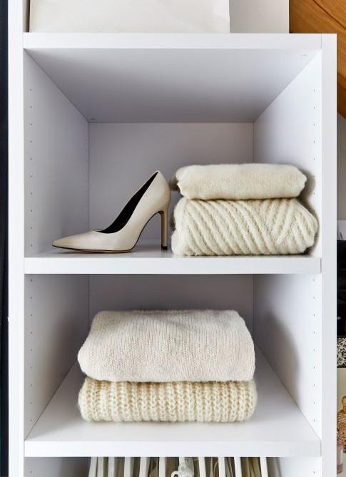 scaffali con maglioni bianchi e scarpe con tacco
