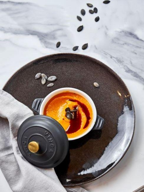 piatto nero con ciotola con zuppa invernale vista dall'alto