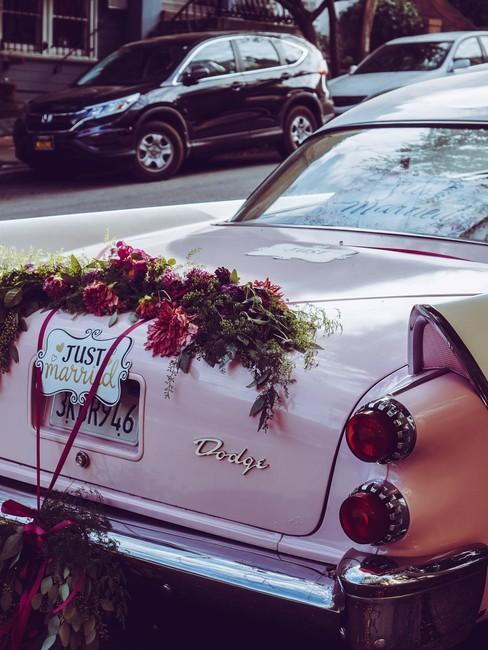 Achterzijde roze oldtimer met trouwaccessoires en bloemen met bordje just married