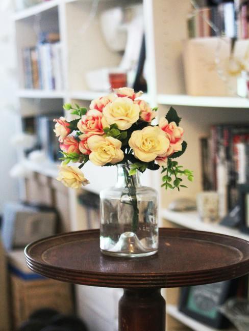 Boeket van kunstrozen in een transparante glazen vaas op een houten bijzettafel op de achtergrond van boekenkast