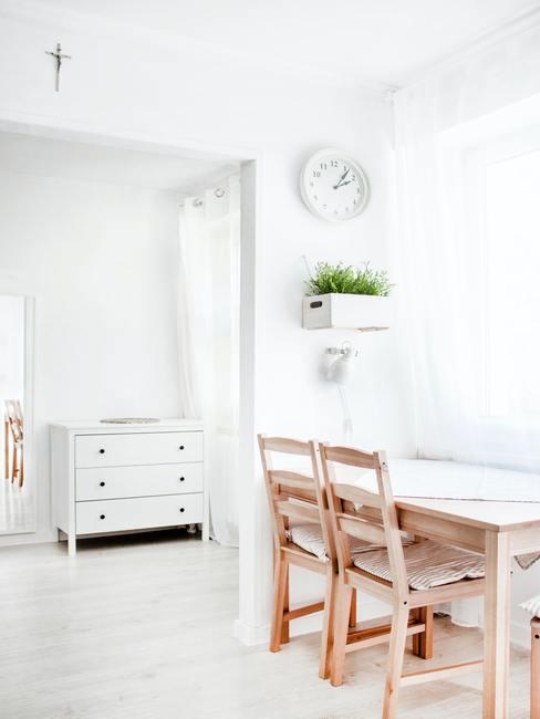 Wit eenvoudig interieur met houten stoelen
