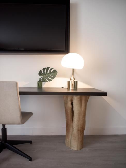 Houten tafel met goudkleurige tafellamp en monstera plant