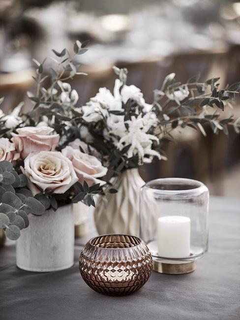 Gedekte bruiloftstafel buiten met veel kaarsen en bloemen in boho-stijl
