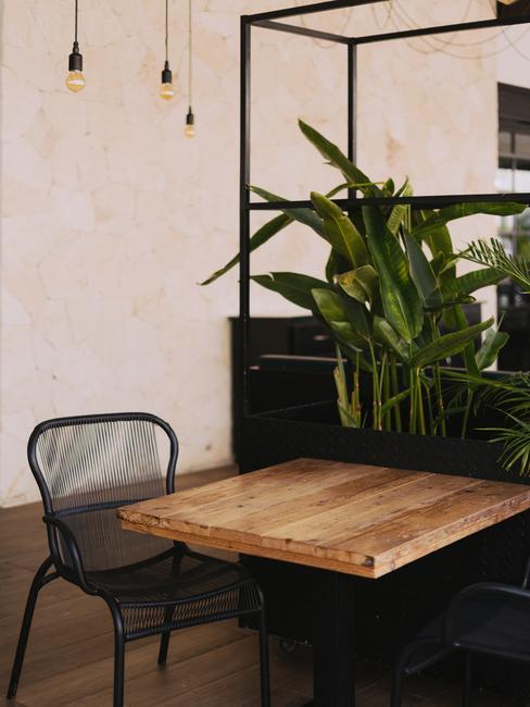 Een houten tafel met een zwarte stoel en een decoratie van planten