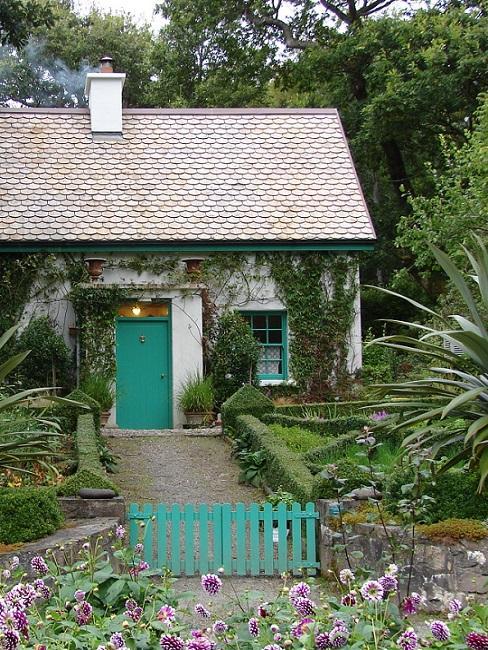 Tuinhuis wit met lila blauw hek en deur met voortuin