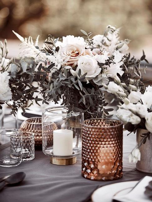 Bloemen en windlichten met kaarsen op tafel in boho stijl buiten trouwlocatie
