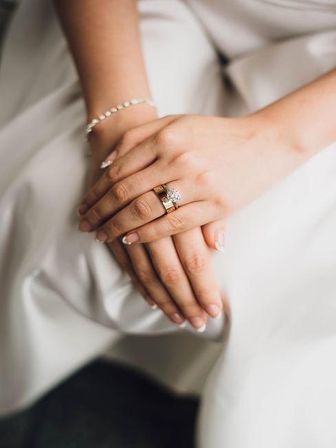 Trouwring op de hand van een vrouw op de schoot van de bruid