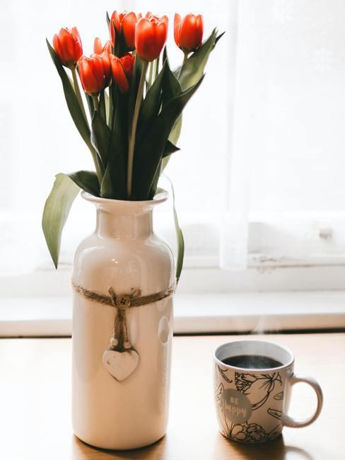Vers gesneden tulpen in een witte vaas op een vensterbank naast koffie