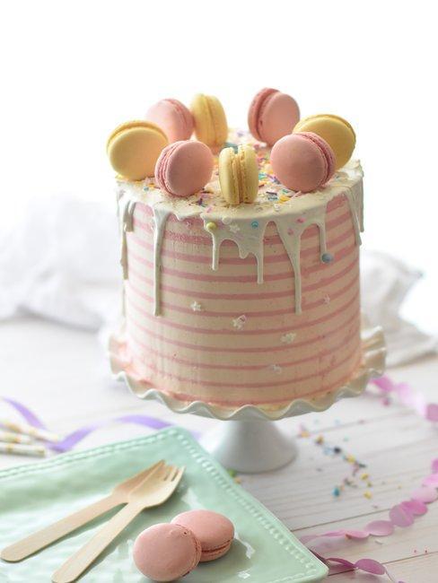 Roze laagjestaart met macarons op witte achtergrond