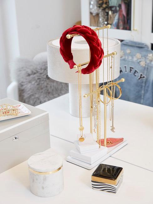 Slaapkamer met witte tafel en sieraden en rode haarband aan een rekje
