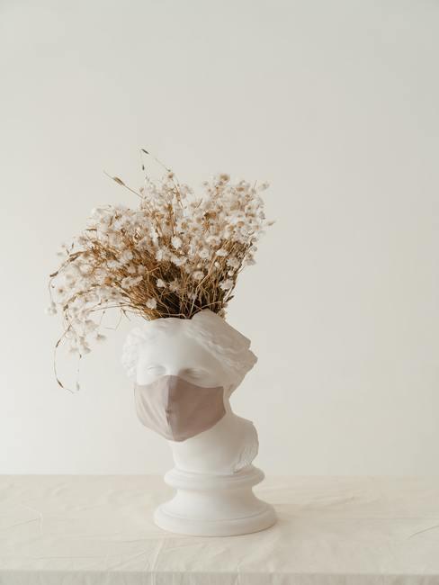 Boeket met droogbloemen in decoratieve vaas op witte dressoir