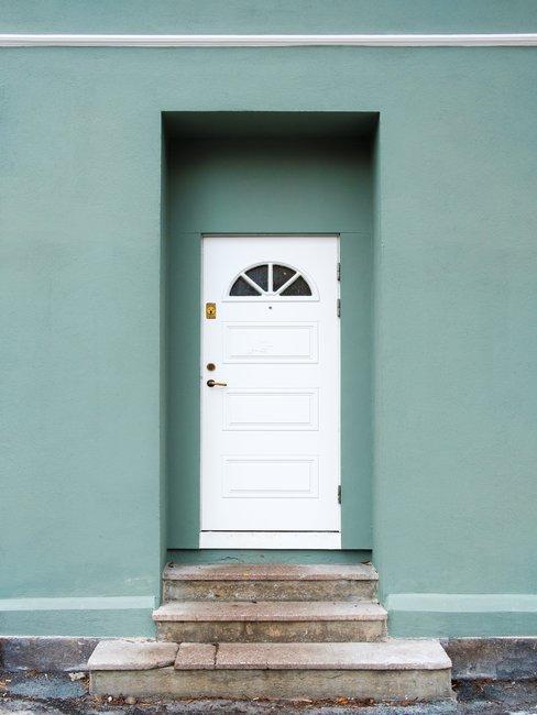 Groenen muur met witte voordeur en bruinen tegeltrap