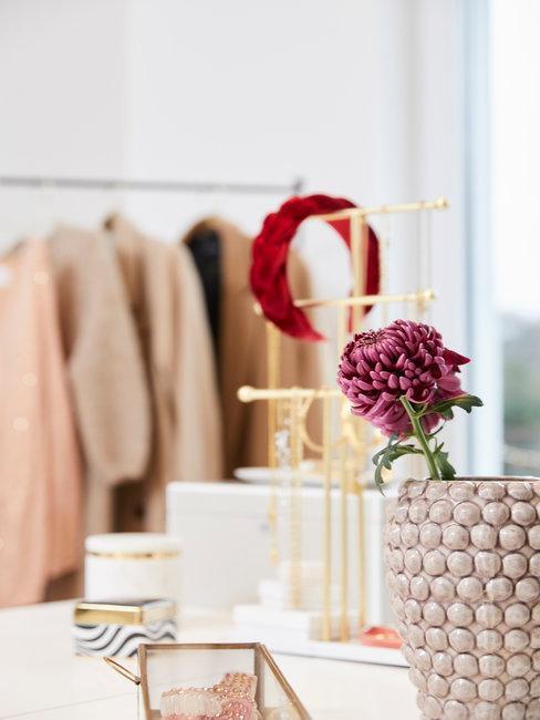Sieraden op hangrek met roze bloem in vaas en op de achtergrond een kledingrek