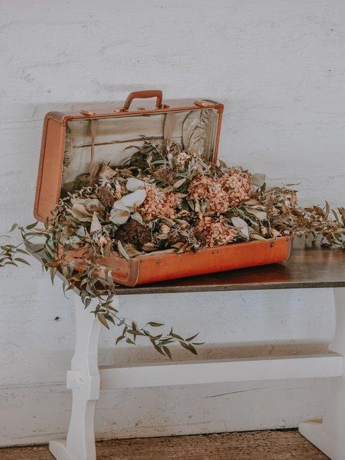 Vintage koffer met droogbloemen op een houten tafel voor een witte muur