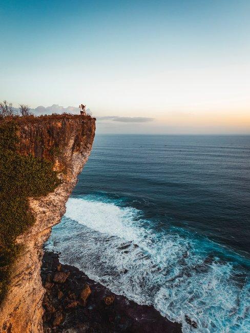 Rots boven de zee met twee mensen en zonsondergang