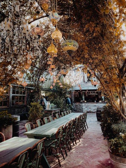 Terras met arabische lampen en groene plantenboog boven lange tafels