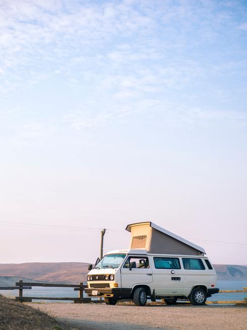Witte bus met uitklapbare dak voor overnachting op een berg met ondergaande zon