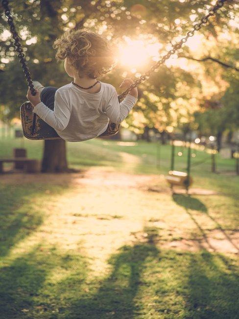 Jongetje op een schommel in het park in de zon