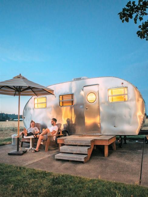 Zilveren camper van de zijkant met een stel op campingstoelen en parasol