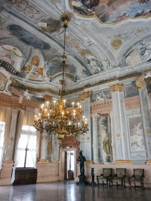 Barokstijl kamer met wandschilderingen in groen en roze tinten met kroonluchter