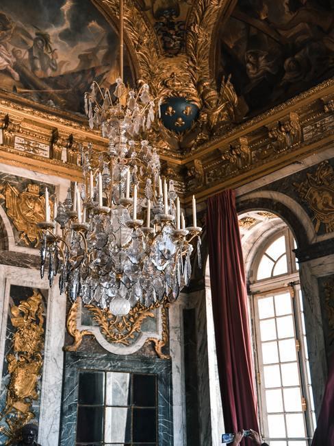 Barokstijl kamer met groot raam met ronde boog aan de boven kant met grote kroonluchter