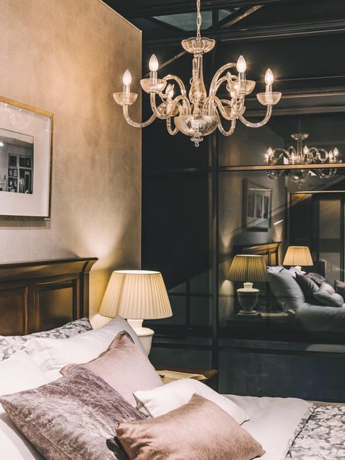 Barokstijl kamer met zwarte wandkast en bed met kroonluchter