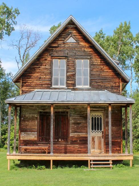 Houten tiny house twee verdiepingen met ramen en een veranda