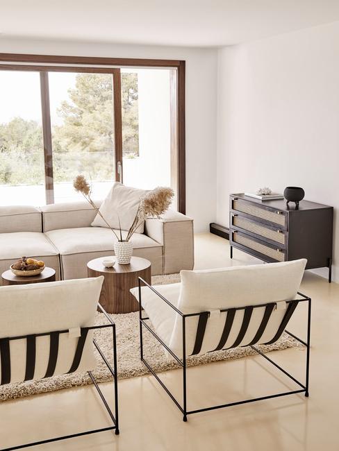 Woonkamer met witte vloer bank en twee stoelen met vloerkleed en retro dressoirkast