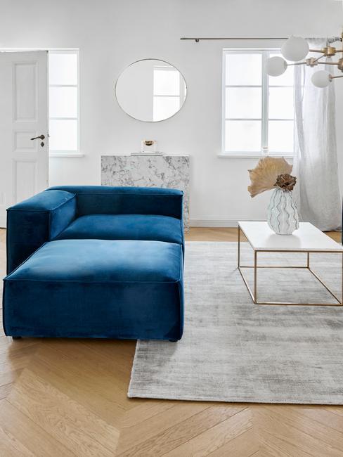 Woonkamer met blauwe bank en visgraat vloer met marmeren asseccoires