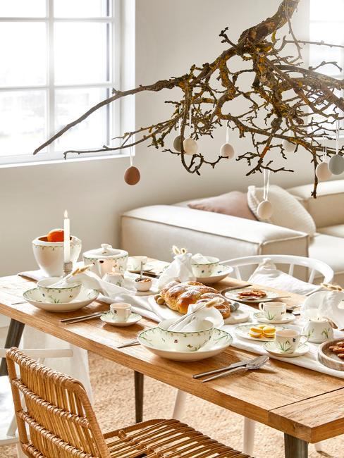 Gedekte licht houten tafel met wit servies en paastak boven de tafel met paaseieren op de achtergrond een witte bank
