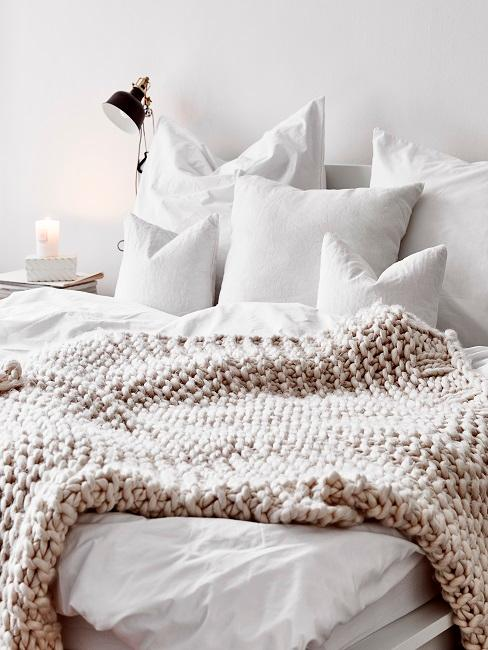 Witte muur met wit bedlinnen en zandkleurige wollen sprei