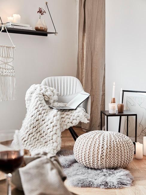 Zandkleur muren met witte en zandkleur accessoires zoals een wollenkleed en poef